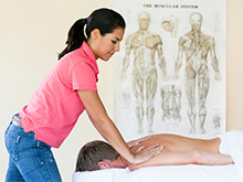 An SSMT student performing massage before an educational poster