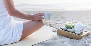 Woman enjoying a cup of tea on the beach