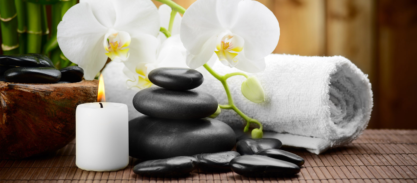 Flowers, towels and a balanced stack of massaging stones