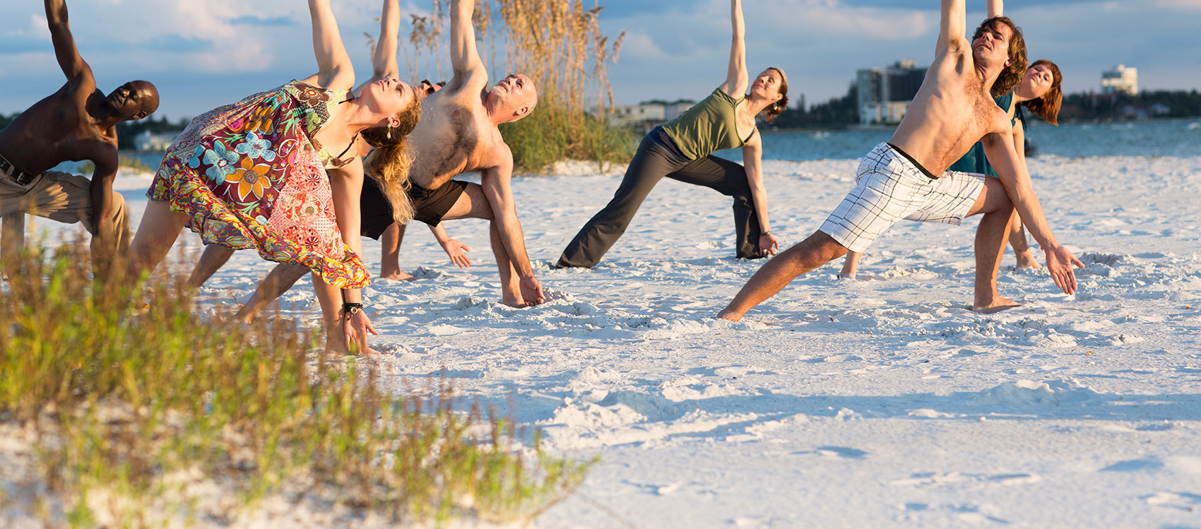 A diverse crowd of people performing yoga on the beach